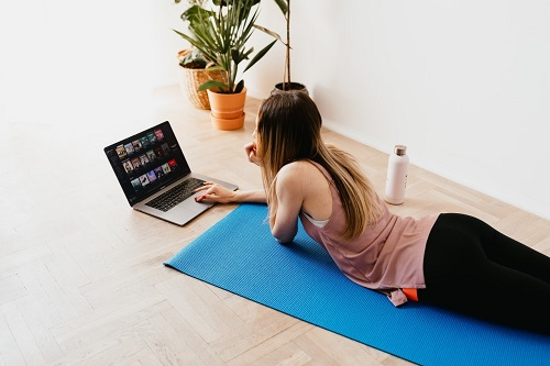 femeie care sta pe saltea si se uita pe laptop