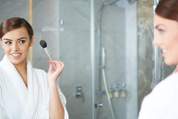 femeie se machiaja in oglinda