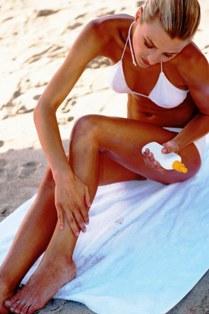Poza femeie care se da cu lotiune de plaja
