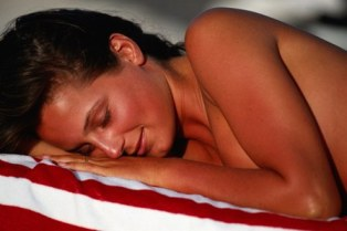 Poza femeie se bronzeaza la mare