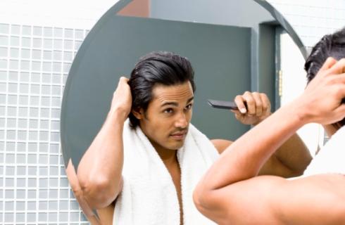 Barbat pieptanandu-se in fata oglinzii
