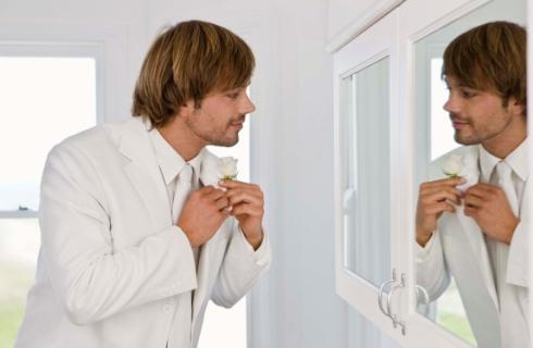 Barbat imbracandu-se in fata oglinzii